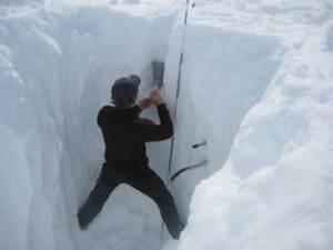 Promice scientist measuring snow density in a snow pit in southern Greenland